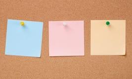 Trzy koloru tapetują notatki na korek desce Zdjęcie Stock