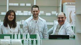 Trzy kompetentnej farmaceuty śmia się w aptece patrzeje kamerę Obrazy Royalty Free
