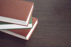 Trzy książki na drewno stole Zdjęcie Royalty Free