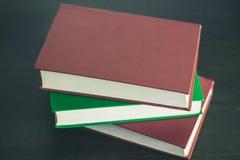 Trzy książki na drewno stole Obraz Stock