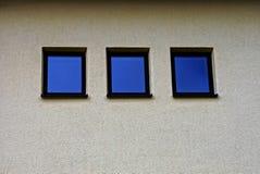 Trzy kwadratowego małego okno na szarej ścianie budynek Obrazy Royalty Free