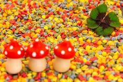 Trzy latać pieczarki i koniczynowego liść na kolorowych confetti Fotografia Stock