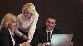 Trzy ludzie biznesu aktywnie dyskutują co widzią w ich laptopie zbiory wideo