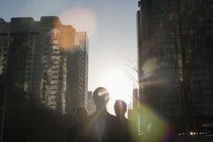 Trzy ludzie biznesu chodzi w dół miasto ulicę z światłem słonecznym przy ich plecy, obiektywu raca zdjęcie stock