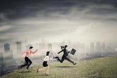 Trzy ludzie biznesu działającej prędkości na wzgórzu Zdjęcia Stock