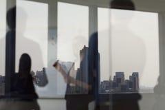 Trzy ludzie biznesu stoi białą deskę na stronie przeciwnej szklana ściana i patrzeje zdjęcia royalty free