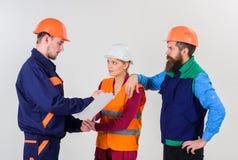 Trzy ludzie dyskutuje nad planem, budowniczowie, inżyniery obraz royalty free