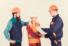Trzy ludzie dyskutuje nad planem, budowniczowie, in?yniery zdjęcie stock