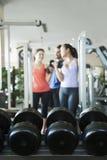 Trzy ludzie podnosi ciężary w gym, ostrość na ciężarach Zdjęcia Royalty Free