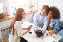 Trzy ludzie siedzą przy stołem Wszystko one są przyglądający kamera Facet trzyma kamerę podczas gdy dziewczyna wewnątrz zdjęcie stock