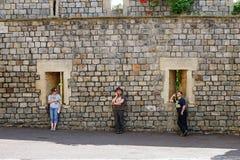 Trzy ludzie stoją równo interliniują podczas gdy na telefonach komórkowych zdjęcia stock