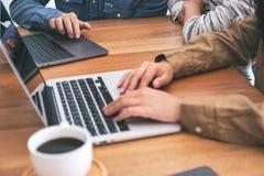 Trzy ludzie używa i pisać na maszynie na laptopie na drewnianym stole obrazy stock