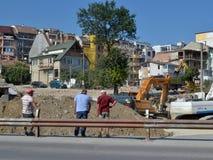 Trzy mężczyzna naradzają się blisko okopu przy miejscem budów drogi pracy blisko budynków mieszkalnych obrazy royalty free