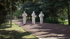 Trzy mężczyzna w hazmat nadają się bieg na kursowym sposobie w parku - zbiory wideo
