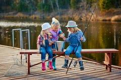 Trzy młodego dziecka przechwalają się o ryba łapiącej na popasie Pojęcie przyjaźń, zabawa wakacje i weekend lub zdjęcia stock