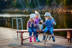 Trzy młodego dziecka przechwalają się o ryba łapiącej na popasie Pojęcie przyjaźń, zabawa wakacje i weekend lub obraz stock
