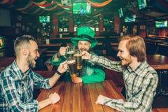 Trzy młodego rozochoconego mężczyzny siedzą przy stołem w pubie i trzymają piwnych kubki wpólnie Facet w środkowym odzieży St Pat fotografia stock