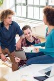 Trzy młodego ucznia używa książkę i pastylka peceta dla sprawdzać informację obrazy royalty free