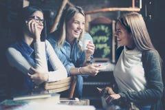 Trzy młodej dziewczyny siedzi w kawiarni i ma rozmowę zdjęcia stock