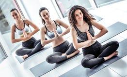 Trzy młodej kobiety medytuje w lotosowej pozie podczas joga klasy w zdrowie klubie obraz royalty free
