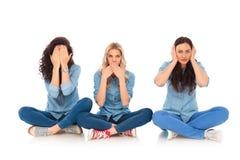 Trzy młodej kobiety robi żadny złu pozują obsiadanie fotografia royalty free