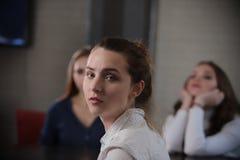 Trzy młodej kobiety w kawiarni Jeden dama siedzi z powrotem kamera Kobiety przyjaźnie i czasu wolnego pojęcie obrazy royalty free
