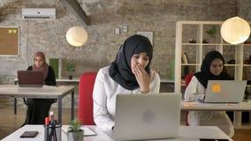 Trzy młodej muzułmańskiej kobiety w hijab działaniu na laptopie w nowożytnym biurze i obsiadaniu, muzułmański kobiety ziewanie, m zbiory
