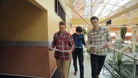 Trzy młodych człowieków spojrzenie przy projektem, dyskutuje, rusza się, zdjęcie wideo