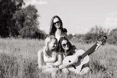 Trzy młodzi ludzie nastoletnich dziewczyn bawić się gitarę Fotografia Stock