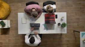 Trzy młodzi ludzie pracuje na laptopie, inny mężczyzna writing na dokumencie w biurze, topshot siedzi przy stołowym i pisać na ma zbiory wideo