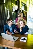 Trzy młodzi ludzie pracuje wpólnie na nowym projekcie Drużyna szczęśliwi biurowi ludzie pracuje na laptopie, ono uśmiecha się Fotografia Stock