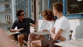 Trzy młodzi ludzie siedzi przy kawiarnią i chattingli zbiory