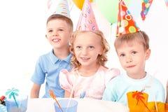 Trzy małego dziecka pozuje podczas przyjęcia urodzinowego zdjęcia royalty free