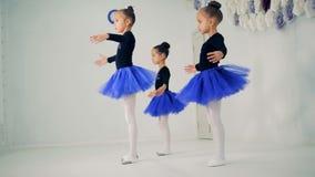 Trzy małej dziewczynki ćwiczą baletniczych ruchy zbiory
