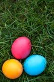 Trzy malowali Wielkanocnych jajka w trawie Zdjęcie Royalty Free