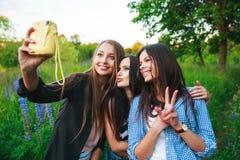 Trzy modniś dziewczyn blondynka i brunetka bierze jaźń portret na polaroid kamerze i ono uśmiecha się plenerowego Dziewczyny ma z Zdjęcie Stock