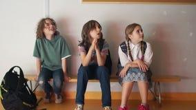 Trzy nastolatka w szkole siedzą na ławce i dostają zanudzającymi Unrecognizable dorosły nauczyciel biega obok i wita uczni dalej zdjęcie wideo