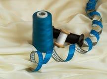 Trzy nici różni kolory i błękitna kręcona taśmy miara na beżowym tiulu tła guzików zbliżenia pojęcia ciemna igielna szwalna nić d Fotografia Royalty Free