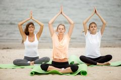 Trzy nikłej młodej dziewczyny siedzą w joga pozy z przymknięć oczami na matach na piaskowatej plaży na ciepłym dniu obrazy royalty free