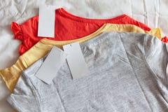Trzy nowa koszulka w few colours z czyst? etykietk? na bia?ym tle Poj?cie zakupy, lato sprzeda?e, rabaty, organicznie bawe?na zdjęcia stock