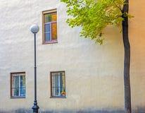 Trzy okno na ścianie dom, latarnia uliczna i drzewo, obrazy royalty free