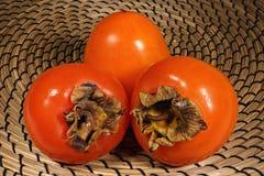 Trzy płodowy persimmon na łozinowym tle obrazy stock