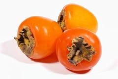 Trzy płodowy persimmon na białym tle fotografia royalty free