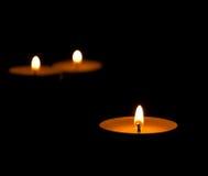 Trzy płonącej świeczki z odbiciem na czarnym tle Obrazy Stock