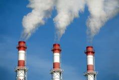 Trzy paskowali przemysłowe drymby z dymem nad bezchmurnym niebieskim niebem Zdjęcia Royalty Free