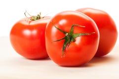 Trzy perfect czerwonego pomidoru na drewnianej desce Fotografia Royalty Free