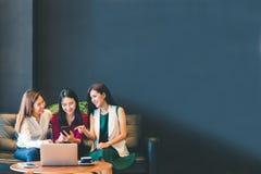 Trzy pięknej Azjatyckiej dziewczyny używa smartphone i laptop gawędzi na kanapie, przy kawiarnią z kopii przestrzenią obrazy stock
