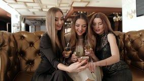 Trzy pięknej dziewczyny patrzeje coś w telefonie przy korporacyjnym przyjęciem zbiory