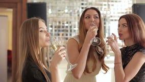 Trzy pięknej dziewczyny tanczy z szkłami szampan w ręce zbiory wideo