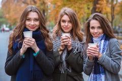 Trzy pięknej kobiety pije kawę outdoors obraz stock